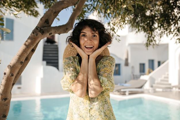 Portrait of happy surprised brunette woman looks at front