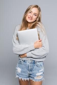Ritratto di donna sorpresa felice in piedi con il computer portatile isolato su sfondo grigio