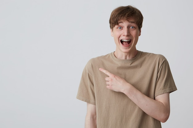 Portrait of happy surprised young man student with metal braces on teeth and opened mouth in beige t shirt