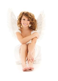 Portrait of happy teenage angel girl over white wall