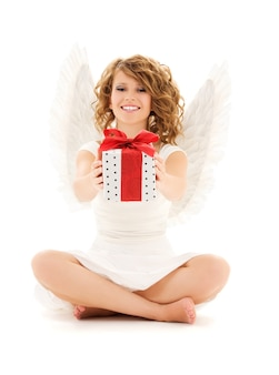 Portrait of happy teenage angel girl with gift over white wall