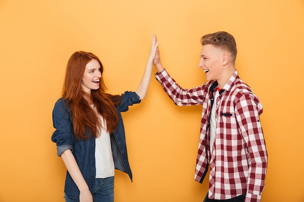 Portrait of a happy teenage couple giving high five