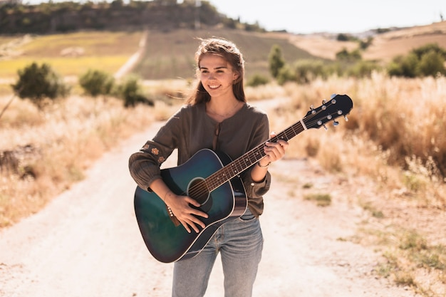 Portrait of a happy teenage girl standing on dirt track playing guitar