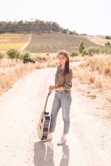 Portrait of a happy teenage girl with guitar standing on dirt track