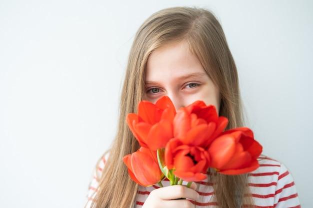 白い壁に立っている赤いチューリップと長い髪の肖像画幸せな10代の少女
