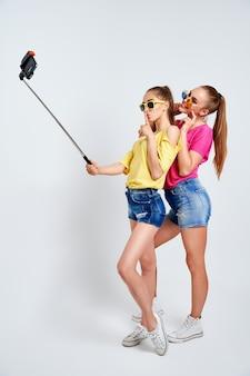 Portrait of happy teenagers taking selfie together isolated on whiteportrait of happy teenagers in summer clothes sunglasses taking selfie together isolated on white
