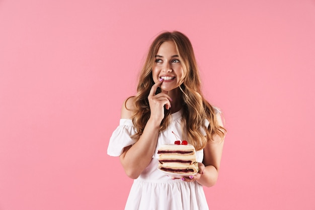 Portrait of happy thinking woman wearing white dress looking upward with her finger on her teethes and holding piece of cake isolated over pink wall