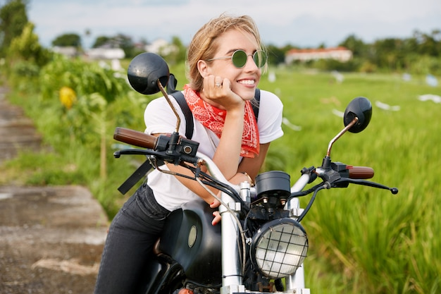 Portrait of happy thoughtful female biker in fashionable sunglasses and casual t shirt, feels free and relaxed as sits on her favorite motorbike and admires landscapes in countryside calm atmosphere