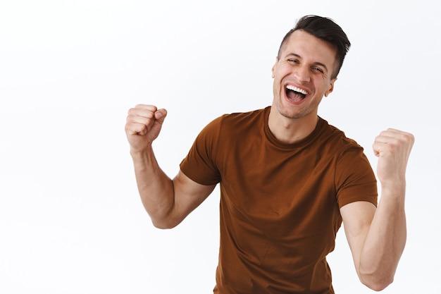 Ritratto di un ragazzo atletico felice e trionfante con bicipiti, mani forti, pompa a pugno e gridando sì, sorridente celebrando la vittoria, raggiungere l'obiettivo o il successo, diventare campione, stare in piedi sul muro bianco