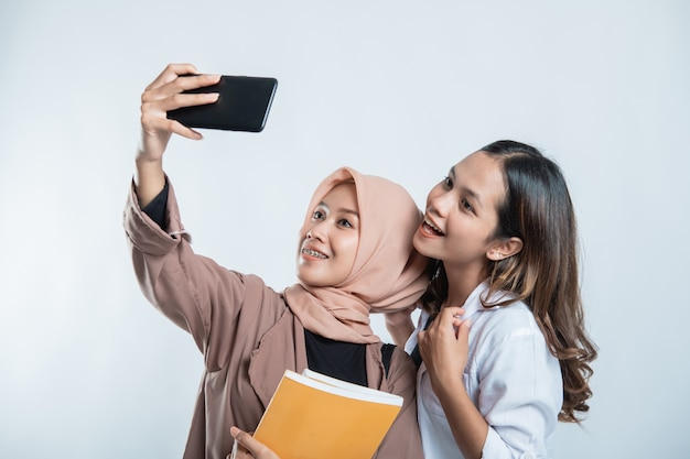 Portrait of happy university youth carrying a bag and taking a selfie with the cellphone on a white isolated