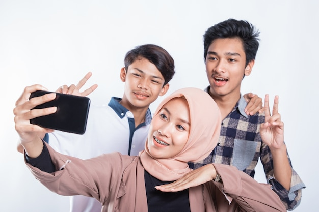 Portrait of happy university youth taking a selfie with the cellphone on a white isolated