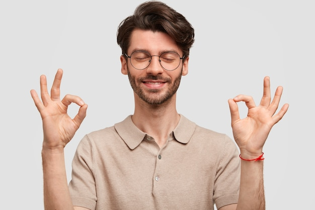Il ritratto di giovane hipster maschio con la barba lunga felice fa il segno giusto