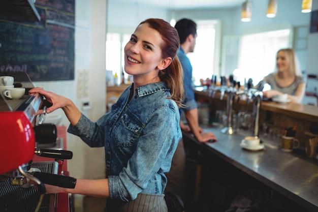 Portrait of happy waitress with co-worker talking to customer at coffee shop
