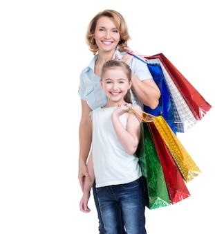 Ritratto della madre bianca felice e della giovane figlia con i sacchetti della spesa isolati