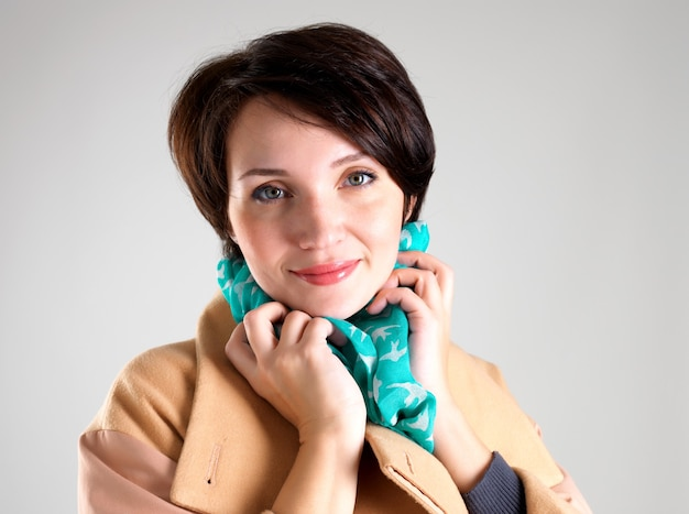 Portrait of happy woman in beige autumn coat with green scarf on grey background