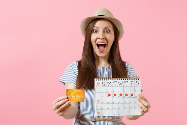 Portrait of happy woman in blue dress, hat holding credit card, periods calendar, checking menstruation days isolated on trending pink background. medical healthcare gynecological concept. copy space.