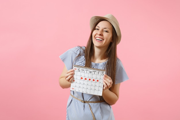 Portrait of happy woman in blue dress, hat holding periods calendar for checking menstruation days isolated on bright trending pink background. medical, healthcare, gynecological concept. copy space.