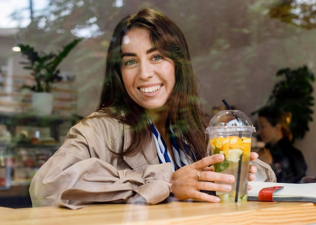 Portrait of happy woman in cafe with fresh lemonade and headphones