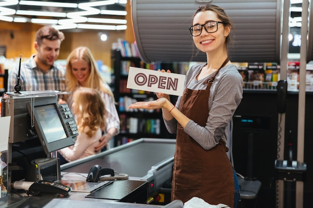 Portrait of happy woman cashier holding open sign
