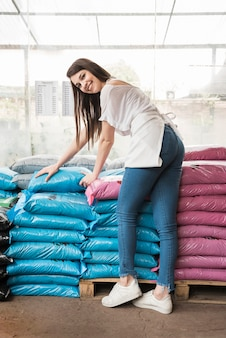 Portrait of a happy woman in front of stacked plastic sacks