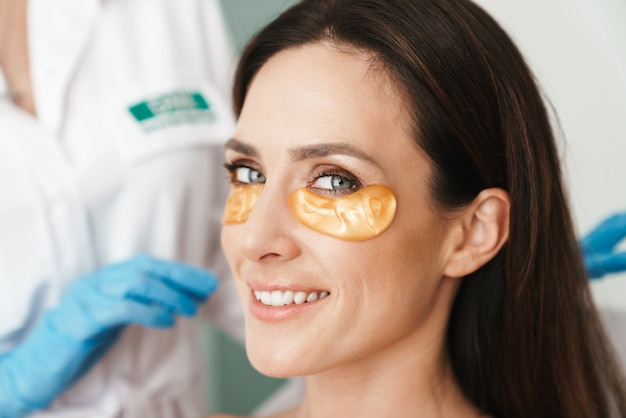 Portrait of happy woman getting cosmetic procedure with patches by specialist in beauty salon