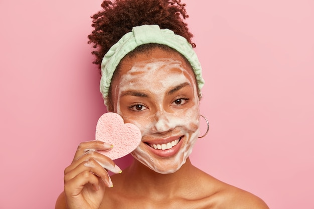 Portrait of happy woman has perfect well cared skin, applies foaming soap for washing face, has pleased expression, holds heart shaped sponge for wiping makeup