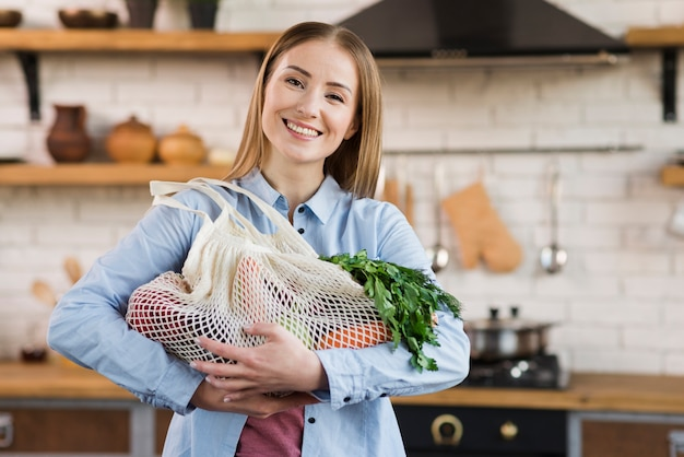 Portrait of happy woman holding bags with organic vegetables