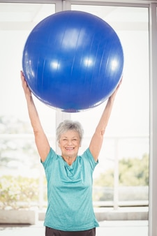 Portrait of happy woman holding blue exercise ball