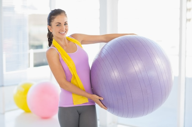 Portrait of happy woman holding exercise ball