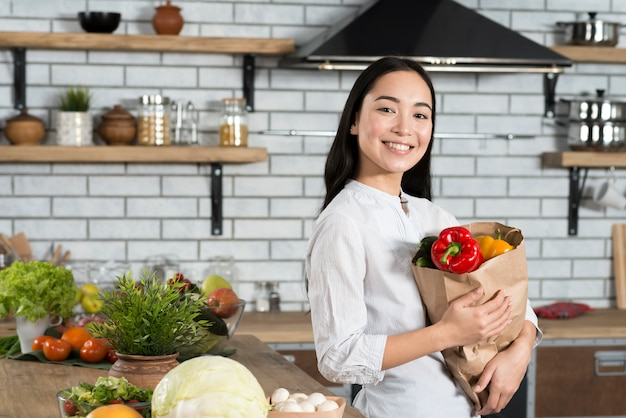 Portrait of happy woman holding grocery bag standing in kitchen