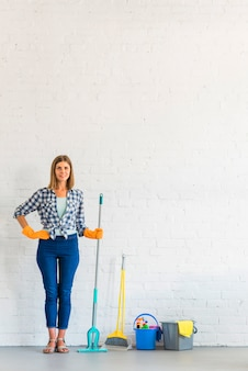 Portrait of a happy woman holding mop in front of brick wall