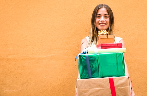 Portrait of a happy woman holding stack of gifts against orange background