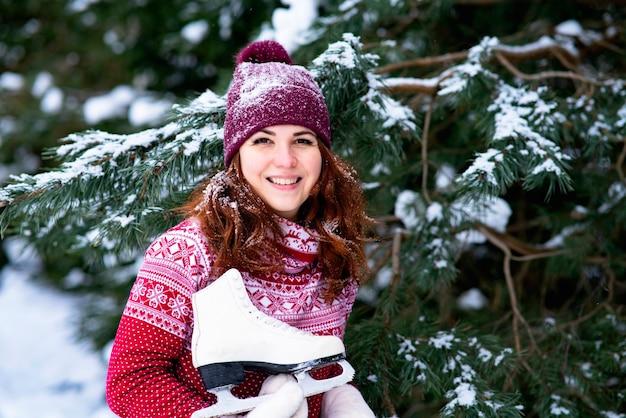 肖像画。雪に覆われた森の中で彼女の肩に冬のスケート靴を保持している幸せな女性。冬の楽しみとスポーツ。