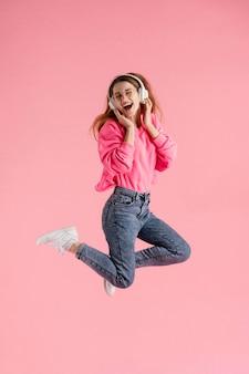 Портрет счастливой женщины прыгает и слушает музыку