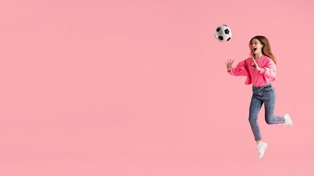 Портрет счастливой женщины прыгает с футбольным мячом