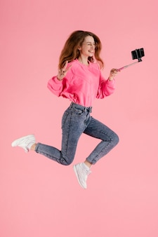 Portrait happy woman jumping with selfie stick