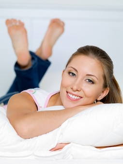 Portrait of happy woman lies on a pillow on the bed
