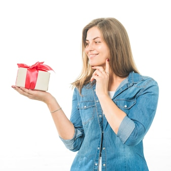 Portrait of a happy woman looking at gift on white background