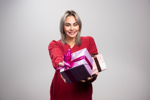 Portrait of happy woman offering gift boxes on gray background.