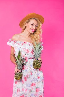 Portrait of happy woman and pineapple over pink background. summer, diet and healthy lifestyle