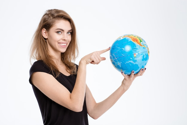 Portrait of a happy woman pointing finger on world globe isolated on a white background