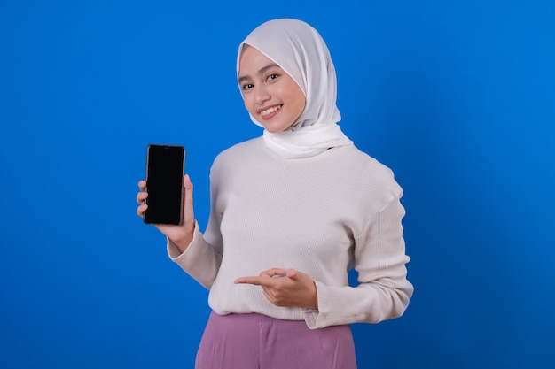 Portrait of a happy woman pointing and holding mobile phone