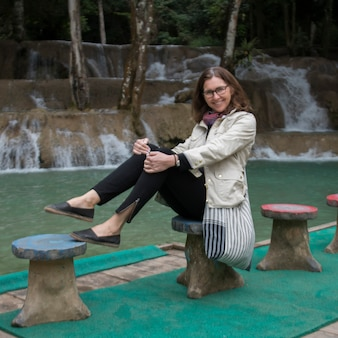 Portrait of happy woman posing near tad sae waterfall, luang prabang, laos