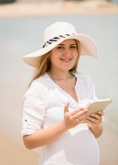 Портрет счастливая женщина позирует с цифровым планшетом на ветреном пляже