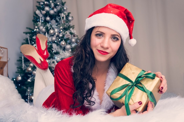 Portrait of happy woman in santa claus cloth hugging many gift boxes on background decorated for christmas apartment. girl with christmas present on the bed is happy and ulybaetsya.