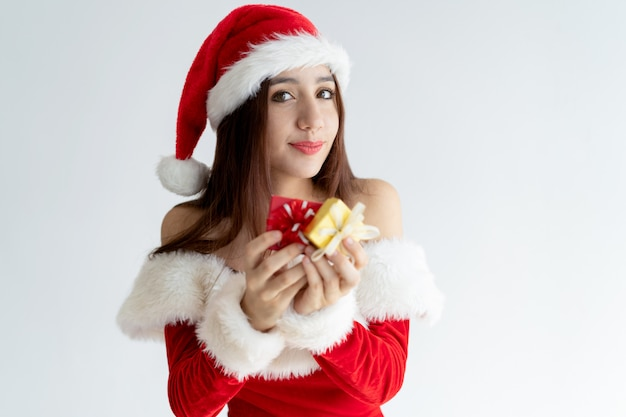 Portrait of happy woman in santa claus dress holding gift boxes