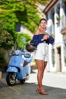 路上で幸せな女のスクータードライバーの肖像画