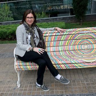 Portrait of a happy woman sitting on bench, santiago, santiago metropolitan region, chile