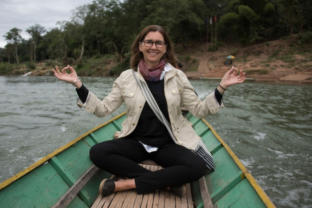 Portrait of happy woman sitting on boat in nam khan river, luang prabang, laos