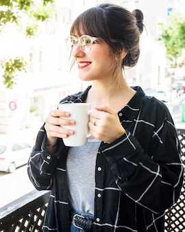 Portrait of a happy woman standing in balcony with cup of coffee
